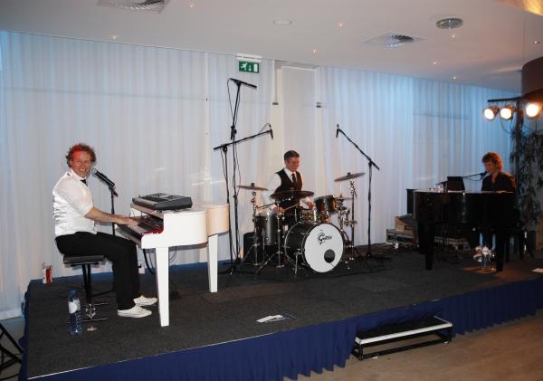 Pumpin Pianos Large met twee pianisten/zangers en een drummer